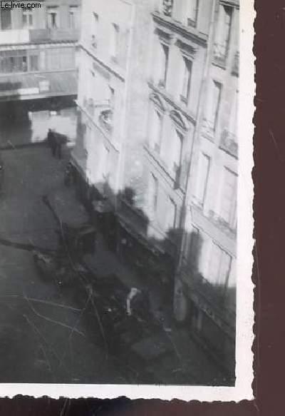 1 PHOTO ARGENTIQUE EN NOIR ET BLANC (légèremetn floue) DE DIMENSION : 7 X 10 Cm : CHUTE D'UN BOMBARDIER AVRO LANCASTER SUR LES MAGASINS DU LOUVRES ET DE SES ENVIRONS A PARIS : VUE SUR LA RUE AVEC MATERIEL MILITAIRE.