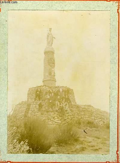 Une photographie originale ancienne en noir et blanc, d'un groupe de 13 hommes au pied d'une statue de Sainte.