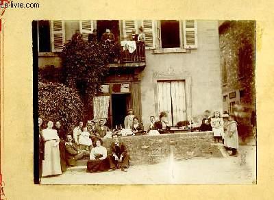 Une photographie originale ancienne en noir et blanc, d'un groupe de villageois dans une ruelle et au balcon, se désaltérant autour de quelques bouteilles de vins.