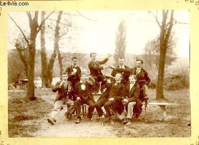 Une photographie originale ancienne en noir et blanc, d'un groupe de 8 hommes autour d'une table, en forêt, dégustant vin et alcool à volonté.
