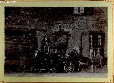 Une photographie originale ancienne en noir et blanc, d'un groupe de 12 personnes (9 hommes et 3 femmes), devant une entrée de maison prenant la pose, avec quelques bouteilles en main. Un homme affalé dans une charrette.