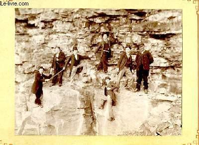 Une photographie originale ancienne en noir et blanc, d'un groupe de 7 hommes, perchés sur une facade rocheuse.
