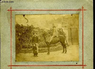 Une photographie originale, en noir et blanc, d'un homme et de 2 enfants, dont l'un chevauchant un cheval.