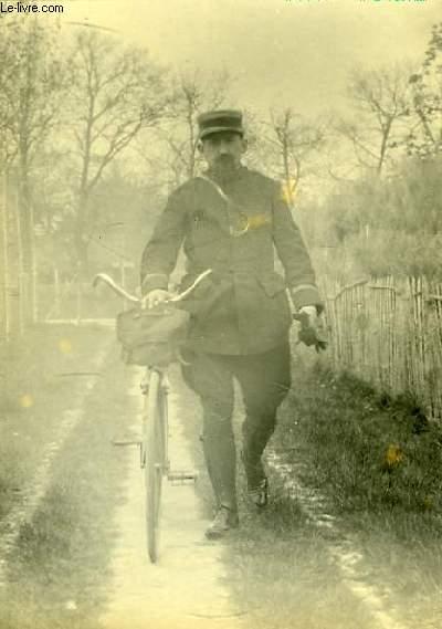 Une photographie originale, en noir et blanc, d'un facteur en tenue, marchant à coté de sa bicyclette.