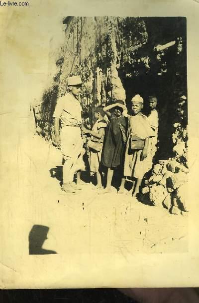Une photographie originale, d'un soldat d'Afrique du Nord avec 4 enfants devant une paroi rocheuse.
